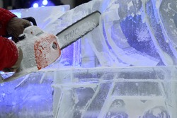 a man sculpts ice with a chain saw to form a transparent barrel
