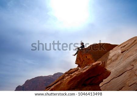 A man seat on the top and look far away, wadi rum, jordan