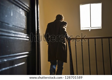 A man seen from behind is going down the staircase in an old parisian building.