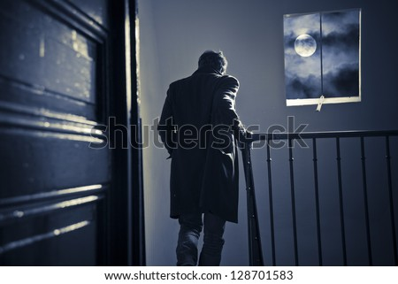 A man seen from behind is going down the staircase in an old parisian building at night. Spooky moon and clouds in the window.