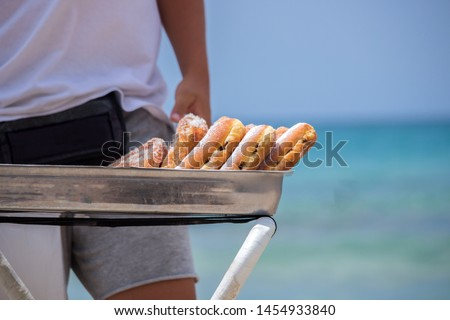 A man selling donuts on the beach