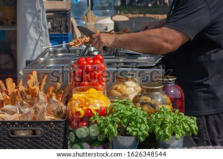 A man sells fresh seasonal vegetables. Tomatoes and basil in the background
