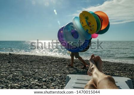A man sells inflatable toys, goes on a pebble beach near the black sea