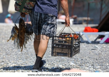 A man sells smoked fish on the beach .