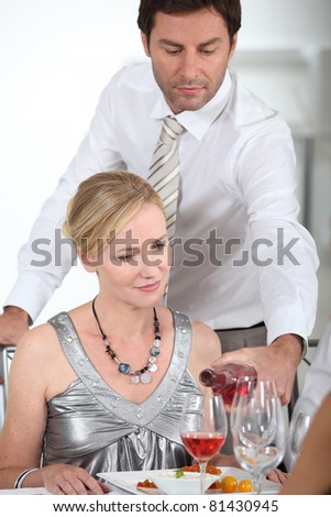 A man serving wine to a woman at the start of a posh dinner.