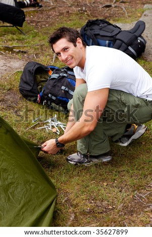 A man setting up a tent on a camping trip