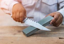 A man sharpens a knife hiking with a whetstone.