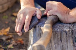 A man sharpens an axe with a whetstone. Weapon.