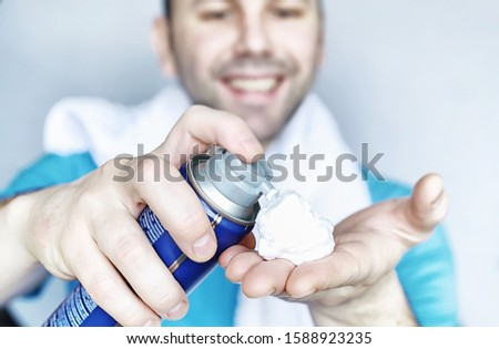 A man shaves in front of a mirror. Shaving foam. Disposable razor.