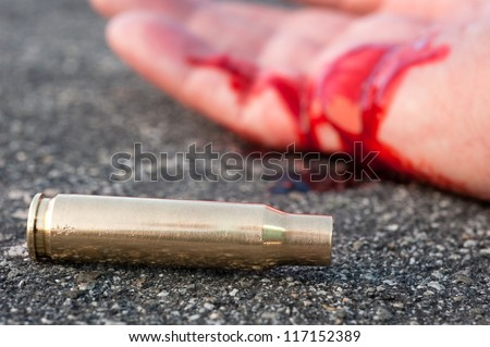 A man shot in the streets with the bullet casing laying next to a bloody hand. - stock photo