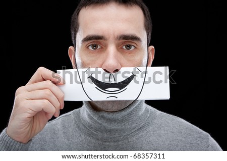 A man showing a blank, indifferent expression, holding a paper with a smile drawn on it in front of his face.