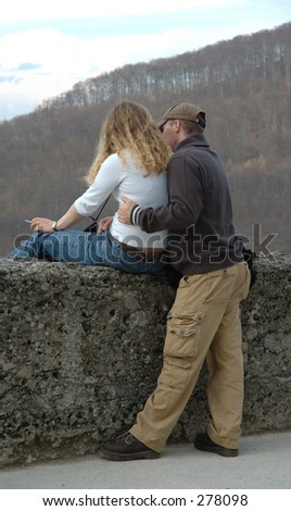 A man shows the woman landscape on old wall