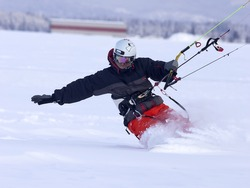 A man shreds snow on a snowboard while snow kiting.