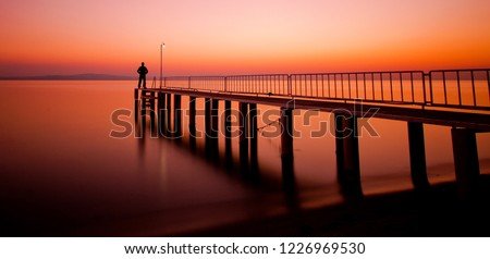 A man silhouette standing on wooden pier lonely at the sea with beautiful bloody sunset. long exposed sunset seascape at a wooden jetty.