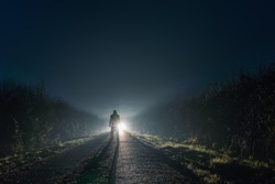 A man silhouetted against a mysterious bright light, glowing on a country lane, surrounded by hedgerows on a winters night.