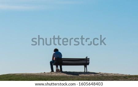 A man sits alone on a bench under a blue sky.