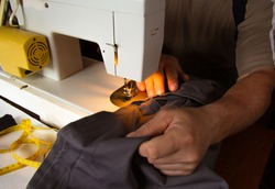 A man sits behind a sewing machine and makes a line on his trousers. He has not yet finished. He is sewing at home.
