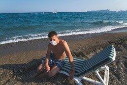 a man sits in a deckchair wearing a mask alone by the sea during the covid 19 flu epidemic