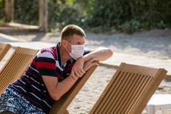 a man sits in a deckchair wearing a mask alone on the beach during the covid 19 flu epidemic