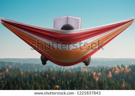 A man sits in a hammock and reads a book in a picturesque place. Back view #1225837843