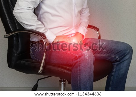 A man sits in an office chair and holds on to the groin, crotch, prostatitis Foto stock ©