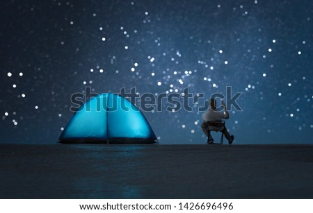 A man sits near a glowing tent and uses a smartphone. #1426696496