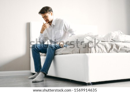 A man sits on a bed indoors with an open window and jeans blankets #1569914635