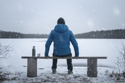 A man sits on a bench on the shore of a frozen lake. Winter. Snow falls. Thermos and a mug are standing nearby. The man is in focus.