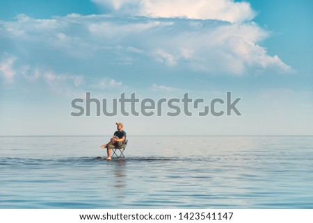 A man sits on a chair in the water.