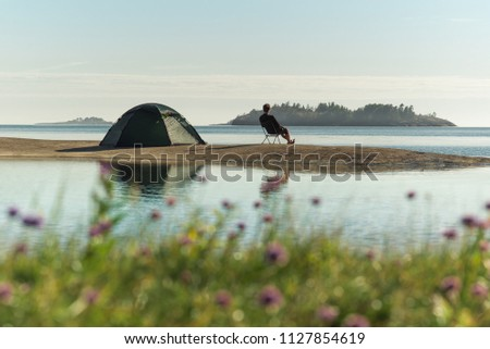 A man sits on a chair on an island and admires a beautiful view. A flowers in the foreground. Calm on the sea #1127854619
