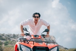 A man sits on a quad in the mountains. Handsome guy in white clothes and a quarter bike on a sandy road against the background of rocks