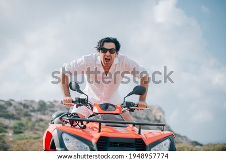 A man sits on a quad in the mountains. Handsome guy in white clothes and a quarter bike on a sandy road against the background of rocks Stock photo ©
