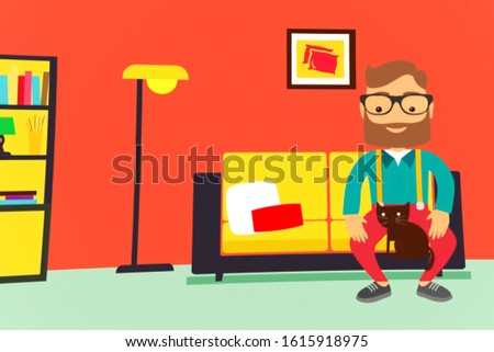 A man sits on the couch with a cat in his apartment