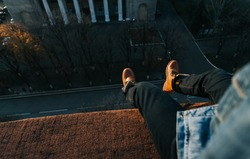 A man sits on the edge of the roof with his legs dangling.