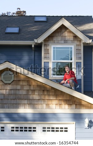A man, sits on top of his roof, holding a power drill, repairing his roof, staring at the camera, smiling. Vertically framed shot.