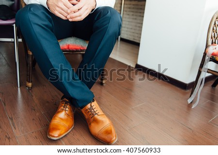 a man sits with hands clasped . View from above