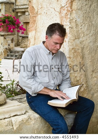 A man sitting and reading what appears to be a bible.
