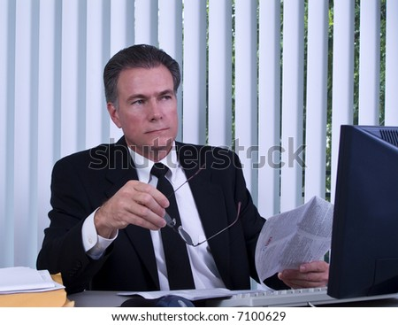 A man sitting at a computer as if pondering the content of the document he is reviewing.