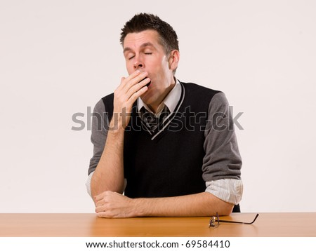 A man sitting at a desk and yawning - stock photo