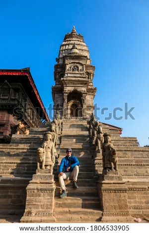 A man sitting at the staircase leading to one of the temples in Bhaktapur, Nepal. On both sides of the stairs there are Hindu Gods, guarding the entrance to the temple. The guardians are really big. Photo stock ©