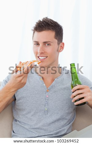 A man sitting down and smiling as he holds some beer and pizza in his hands