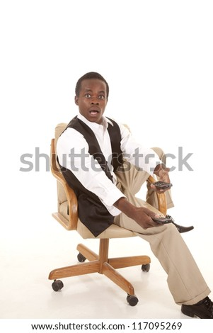 A man sitting in his chair with two remotes with a shocked expression his face at what he just saw.