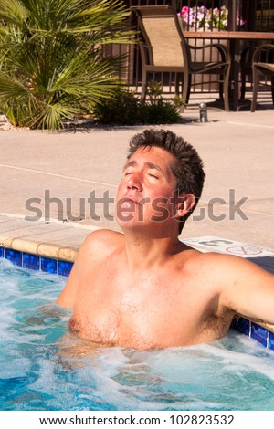 A man sitting in the hot tub with eyes closed and face tilted up to enjoy the sunshine