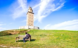 A man sitting on a bench looking The Hercules tower in La Coruna, Galicia, Spain, UNESCO