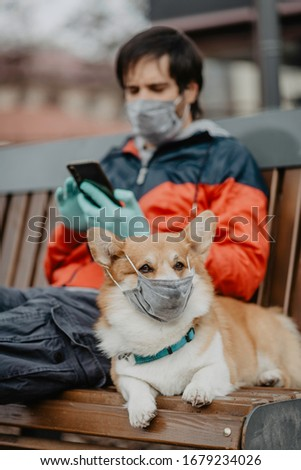A man sitting on a bench with a dog wearing masks dialing a number on a cell phone