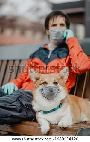 A man sitting on a bench with a dog wearing masks talking on a cell phone