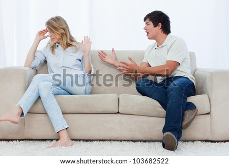 A man sitting on a couch is having an argument with his girlfriend who has her head turned away - stock photo