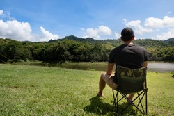 A man sitting on foldable camping chair relaxed outside a tent with camping lake background.