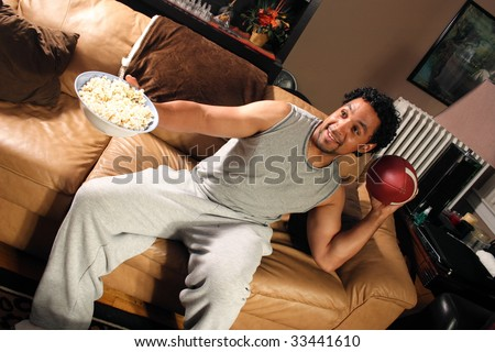 A man sitting on his couch with a bowl of popcorn set up to throw a football
