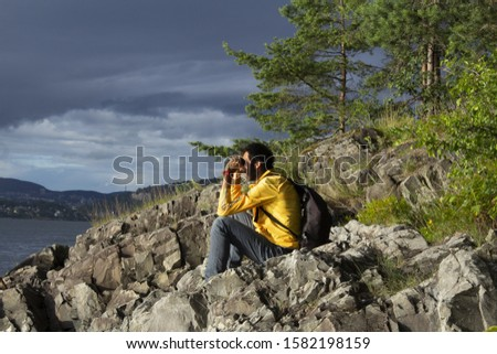 A man sitting on some rocks of a cliff watching something on the horizon of an island in the Norwegian fjords. He wears sport wear and takes a backpack. Highlights the color of his yellow windbreaker